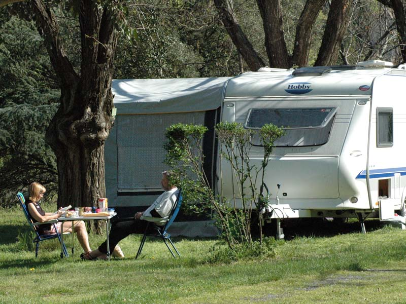 A couple have breakfast next to their caravan