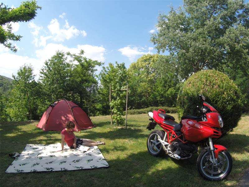 A woman reads a book on her pitch, between her tent and her motorbike