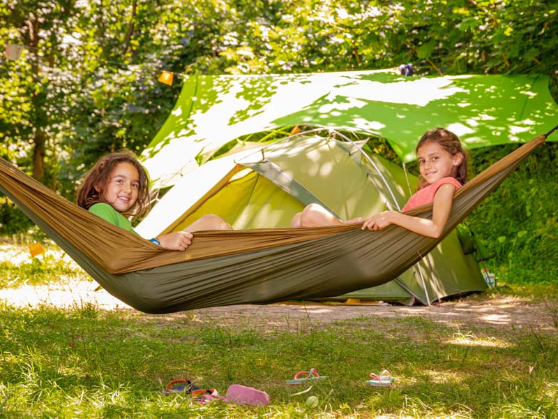 Children in a hammock in front of a tent