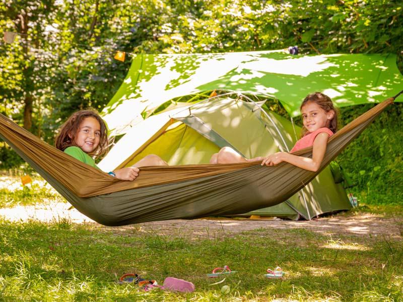 Kinder in einer Hängematte vor einem Zelt
