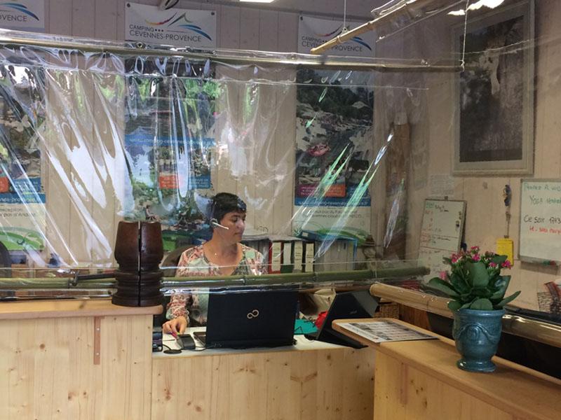 Nathalie à la réception derrière la bache en bambous